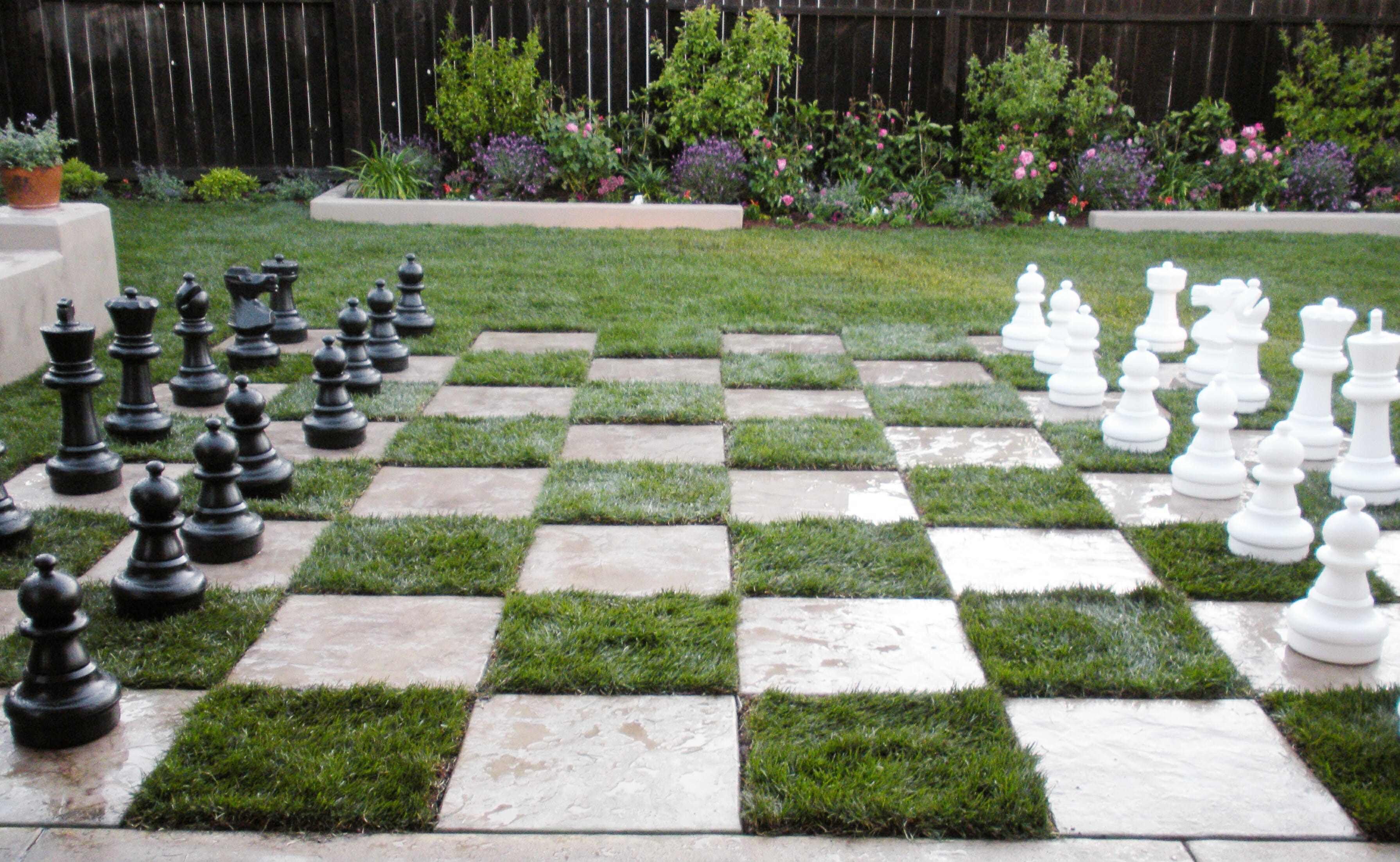 This yard becomes the ultimate entertaining space with the addition of a concrete and sod checkered patio with built-in benches and giant chess pieces.
